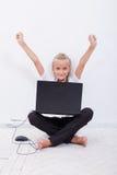 La giovane ragazza teenager con le armi si è alzata per mezzo del computer portatile Fotografia Stock Libera da Diritti
