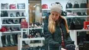 La giovane ragazza teenager sceglie le sue scarpe nel deposito video d archivio