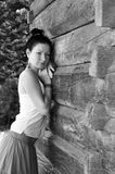 La giovane ragazza thoughful fa una pausa la parete di legno Immagine Stock