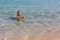 La giovane ragazza turistica in vetri di sport di nuoto sta galleggiando nel mar Egeo sulla costa della penisola di Sithonia immagine stock