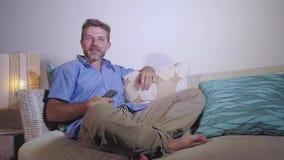La giovane seduta caucasica attraente dell'uomo 30s o 40s realxed a casa lo strato del sofà che guarda la risata della TV felice archivi video