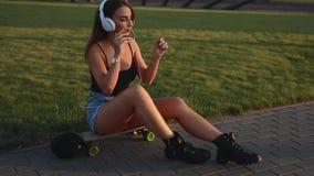 La giovane seduta della donna del skateboarder e mette sopra le cuffie stock footage