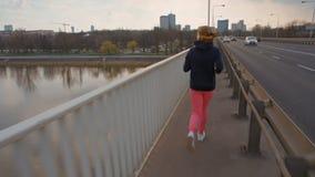La giovane signora in abiti sportivi sta correndo su un ponte sui precedenti della città stock footage