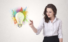 La giovane signora che disegna una lampadina variopinta con variopinto spruzza Fotografia Stock