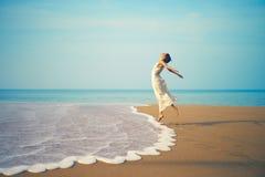 La giovane signora che salta sulla spiaggia Immagine Stock