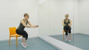 La giovane signora fa gli esercizi per le gambe con la sedia video d archivio