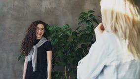 La giovane signora graziosa con capelli ricci scuri lunghi sta posando con la grande pianta verde mentre il fotografo sta sparand video d archivio