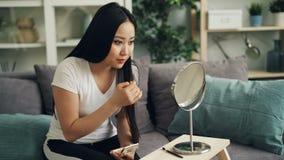 La giovane signora graziosa sta mettendo su trucco facendo uso di cipria poi che guarda in specchio e che segna suo godere dei ca archivi video