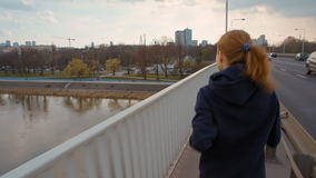 La giovane signora piacevole con la coda di cavallo in abiti sportivi sta correndo su un ponte nella città stock footage