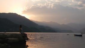 La giovane signora si siede su un bordo di roccia vicino al lago video d archivio