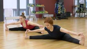 La giovane signora sta avendo classe di yoga con il suo istruttore femminile maturo in palestra moderna, movimento lento stock footage