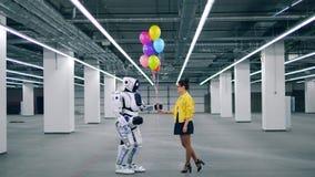 La giovane signora sta dando i palloni ad un cyborg del tipo di umana stock footage