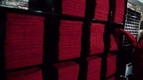 La giovane signora sta prendendo l'asciugamano rosso dalle azione in scaffali neri nel centro sportivo di lusso, movimento lento archivi video