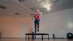 La giovane signora sta saltando su Mini Trampoline durante l'allenamento di forma fisica nella palestra archivi video