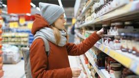 La giovane signora sta selezionando un barattolo con inceppamento nel deposito del supermercato stock footage