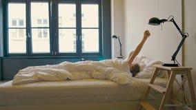La giovane signora sta svegliando in un letto, allungantesi in un hotel nel mornin archivi video