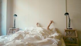 La giovane signora sta svegliando in un letto bianco e sta allungandosi di mattina video d archivio