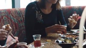 La giovane società è divertentesi e mangiante nella barra fumo del narghilé, comunicante in un ristorante orientale video d archivio