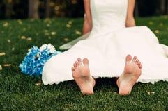 La giovane sposa bionda scalza si siede sull'erba in un parco esotico Immagine Stock