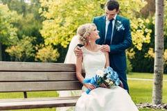 La giovane sposa bionda si siede su un banco accanto allo sposo in un parco esotico Immagine Stock Libera da Diritti
