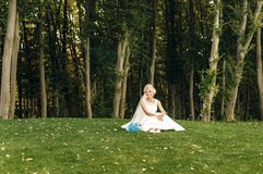 La giovane sposa bionda si siede sull'erba Immagini Stock