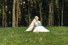La giovane sposa bionda si siede sull'erba Fotografia Stock