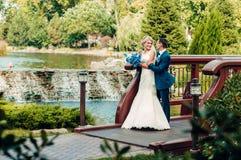 La giovane sposa bionda sta accanto allo sposo in un parco esotico Immagini Stock
