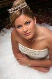 La giovane sposa si è vestita nella seduta bianca sul pavimento Immagine Stock