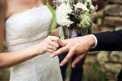 La giovane sposa sta riparando una fede nuziale fotografia stock libera da diritti