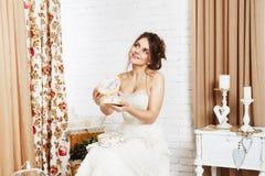 La giovane sposa in vestito da sposa apre il presente Fotografie Stock
