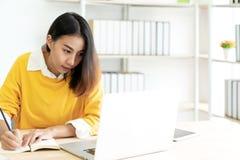 La giovane studentessa asiatica attraente che si siede alla tavola che esamina il giornale di scrittura del computer portatile no immagini stock