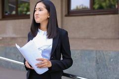 La giovane studentessa asiatica della femmina adulta tiene nei documenti o delle mani Immagini Stock