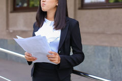 La giovane studentessa asiatica della femmina adulta tiene nei documenti o delle mani Fotografia Stock Libera da Diritti
