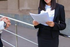 La giovane studentessa asiatica della femmina adulta tiene nei documenti o delle mani Immagini Stock Libere da Diritti