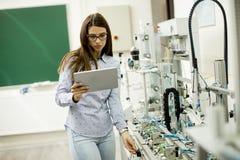 La giovane studentessa di robotica sta in un laboratorio Fotografia Stock