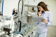 La giovane studentessa di robotica sta in un laboratorio Immagini Stock