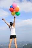 La giovane tenuta asiatica della donna ha colorato i palloni sul picco di montagna Fotografie Stock Libere da Diritti