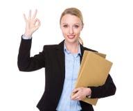 La giovane tenuta della donna di affari con la cartella ed il segno giusto gesture Immagine Stock