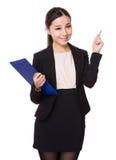 La giovane tenuta della donna di affari con la lavagna per appunti ed il dito indicano su Fotografia Stock Libera da Diritti