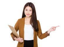 La giovane tenuta della donna di affari con la lavagna per appunti ed il dito indicano via Immagine Stock