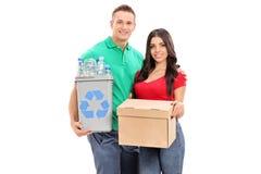 La giovane tenuta delle coppie ricicla il recipiente e una scatola Fotografia Stock