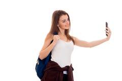 La giovane tenuta sorridente della ragazza sul suo zaino della spalla e si spara sul telefono Immagine Stock Libera da Diritti