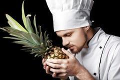 La giovane uniforme barbuta di bianco di In del cuoco unico dell'uomo tiene l'ananas fresco su fondo nero Immagini Stock
