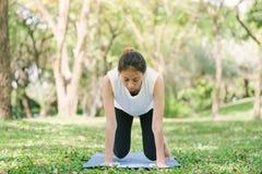 La giovane yoga asiatica della donna all'aperto tiene la calma e medita mentre pratica l'yoga per esplorare la pace interna fotografia stock