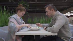 La giovani bei donna ed uomo stanno mangiando l'insalata di caesar in un caffè archivi video