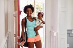 La giovani donna di colore e bambino arrivano a casa dopo l'esercitazione fotografia stock