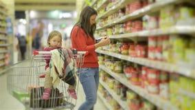 La giovani madre e bambino cammina lungo gli scaffali all'ingrosso e prendendo le merci in carrello del negozio, la donna sta vic video d archivio