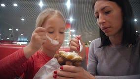 La giovani madre e figlia mangiano il gelato in un caffè Buone relazioni del genitore e del bambino Momenti felici insieme famigl stock footage