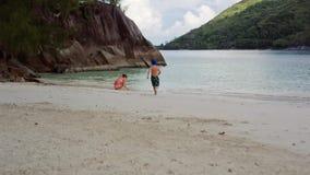 La giovani madre e figlio raccolgono le coperture sulla spiaggia nella laguna sulle Seychelles stock footage