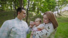 La giovani mamma e papà allattano con il biberon i bambini nel parco sulle loro mani archivi video
